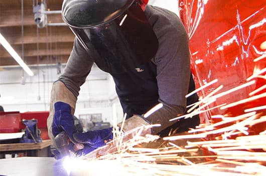 man welding with sparks flying off of metal